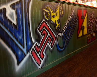 Wall displaying spray paint artwork of local college logos